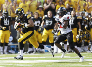 Photo - Iowa wide receiver Jordan Cotton, left, runs from Northern Illinois cornerback Sean Evans after catching a 53-yard pass during the first half of an NCAA college football game, Saturday, Aug. 31, 2013, in Iowa City, Iowa. (AP Photo/Charlie Neibergall)