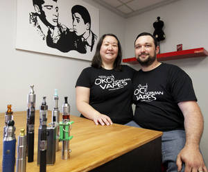 Photo - Stephanie and John Durst pose with some of their more elaborate e-cigarette products in the OKC Vapes store located on 3710 NW 50th St. in Oklahoma City. Photo by Aliki Dyer,  The Oklahoman