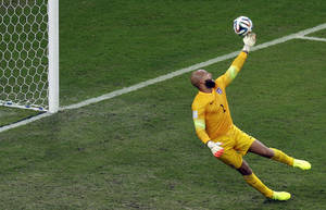 Photo - United States' goalkeeper Tim Howard tips a ball to deflect it over the goal during the group G World Cup soccer match between the USA and Portugal at the Arena da Amazonia in Manaus, Brazil, Sunday, June 22, 2014. (AP Photo/Themba Hadebe)