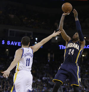 Photo - Indiana Pacers' Paul George (24) shoots over Golden State Warriors' Klay Thompson during the second half of an NBA basketball game Monday, Jan. 20, 2014, in Oakland, Calif. (AP Photo/Ben Margot)