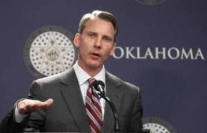 Photo - Oklahoma state Treasurer Ken Miller, seen in this AP file photo, gestures during a news conference in Oklahoma City, Tuesday, April 3. Miller says Oklahoma's two-year revenue growth streak has come to an end. (AP Photo/Sue Ogrocki)