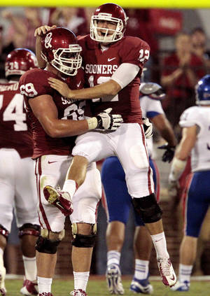 photo - CELEBRATION: Landry Jones celebrates a touchdown throw with Lane Johnson (69) during the second half of the college football game where the University of Oklahoma Sooners (OU) defeated the University of Kansas Jayhawks (KU) 52-7 at Gaylord Family-Oklahoma Memorial Stadium in Norman, Okla., on Saturday, Oct. 20, 2012. Photo by Steve Sisney, The Oklahoman