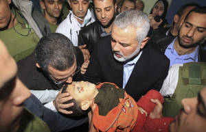 photo -   Gaza's Hamas Prime Minister Ismail Haniyeh, right, and Egyptian Prime Minister Hesham Kandil, left, hold the body of a Palestinian boy they claim was killed in an Israeli strike on Gaza City, as they show the body to the media at Shifa hospital in Gaza City, Friday, Nov. 16, 2012. Neighbors said the boy was killed in a blast around 8:30 a.m. Friday, around the time Kandil was entering the territory. Israel, which ordinarily confirms strikes, vociferously denied carrying out any form of attack in the area since the previous night. (AP Photo/Mahmud Hams, Pool)