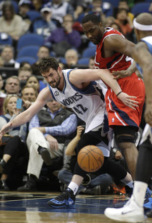 Photo - Minnesota Timberwolves forward Kevin Love (42) has the ball knocked away by Atlanta Hawks forward Elton Brand (42) during the first half of an NBA basketball game, Wednesday, March 26, 2014, in Minneapolis. (AP Photo/Paul Battaglia)