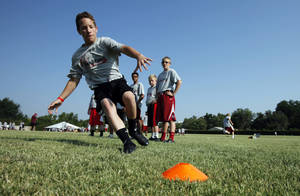 Photo - Keaton Wingo, 14, runs drills at Sam Bradford's Football Camp on the campus of the University of Oklahoma on Wednesday, July 11, 2012, in Norman, Okla.  Photo by Steve Sisney, The Oklahoman