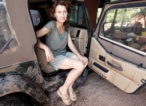 Photo - Above: Mary Wolf sits in her Jeep on Tuesday, wounds visible on her hands, arms and legs. The door and seats of the Jeep are stained with her blood.