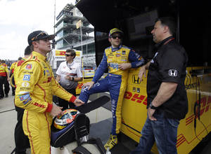 Photo - In this photo taken on May 11, 2014, car owner Michael Andretti, right, talks with drivers Ryan Hunter-Reay, left, and Marco Andretti during practice for Indianapolis 500 IndyCar auto race at the Indianapolis Motor Speedway in Indianapolis. (AP Photo/Darron Cummings)