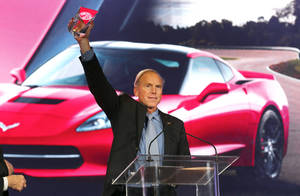 Photo - Chevrolet Corvette Stingray chief engineer Tadge Juechter holds up the North American Car of the Year award at the North American International Auto Show in Detroit, Monday, Jan. 13, 2014. (AP Photo/Paul Sancya)