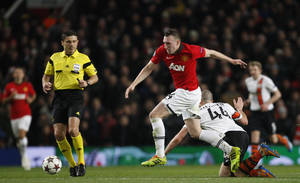 Photo - Manchester United's Phil Jones, centre takes the ballast a falling Donetsk's Yaroslav Rakitskiy during their Champions League group A soccer match between Manchester United and Shakhtar Donetsk at Old Trafford Stadium, Manchester, England, Tuesday, Dec. 10, 2013. (AP Photo/Jon Super)
