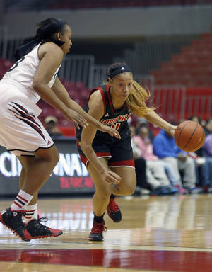 Photo - Louisville guard Antonita Slaughter (4) drives against Cincinnati forward Jeanise Randolph (33) during the first half of an NCAA  college basketball game, Saturday, March 1, 2014, in Cincinnati. (AP Photo/David Kohl)