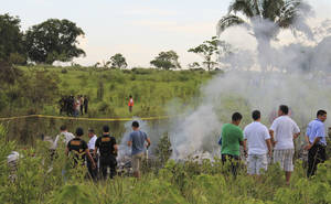 Photo - Investigators stand near the wreckage of a U.S.-owned cargo helicopter in Pucallpa, Peru, Monday, Jan. 7, 2013. Five U.S. citizens are among seven people killed in the crash in the Peruvian jungle. The heavy-lift, twin-rotor Chinook BH-234 chopper, owned by Columbia Helicopters in the Portland suburb of Aurora, Oregon, crashed Monday shortly after taking off from the provincial capital of Pucallpa bound for Tarapoto. (AP Photo/Noe Nole)