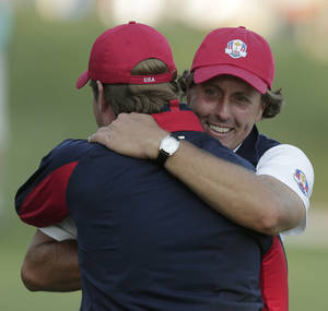 Photo -   USA's captain Davis Love III hugs Phil Mickelson on the 17th hole after winning a four-ball match at the Ryder Cup PGA golf tournament Friday, Sept. 28, 2012, at the Medinah Country Club in Medinah, Ill. (AP Photo/Charlie Riedel)