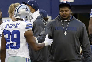 photo - Dallas Cowboys suspended player Josh Brent, right, is greeted by DeMarco Murray (29) on the sideline during the first half of an NFL football game against the Pittsburgh Steelers Sunday, Dec. 16, 2012 in Arlington, Texas. Brent was the driver in a car crash that killed teammate Jerry Brown, Jr.(AP Photo/LM Otero)