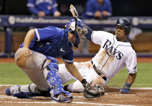 Photo - Tampa Bay Rays' Desmond Jennings, right, scores past Toronto Blue Jays catcher Josh Thole during the fifth inning of a baseball game Monday, March 31, 2014, in St. Petersburg, Fla. Jennings scored on a double by teammate Matt Joyce. (AP Photo/Chris O'Meara)