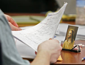 Photo -   Brogan Rafferty, 17, sorts papers at the defense table next to a photo of Jesus Christ propped up on a pair of eyeglasses during his murder trial in the Summit County Common Pleas courtroom in Akron, Ohio on Friday, Oct. 12, 2012. Rafferty and an adult accomplice are charged with three killings in a plot to lure victims through phony Craigslist job offers. (AP Photo/Akron Beacon Journal, Phil Masturzo)