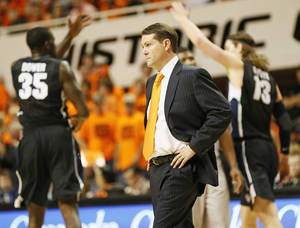 photo - CELEBRATION: OSU head coach Travis Ford walks on the court during a timeout as Gonzaga's Sam Dower (35) and Kelly Olynyk (13) celebrate during a men's college basketball game between Oklahoma State University (OSU) and Gonzaga at Gallagher-Iba Arena in Stillwater, Okla., Monday, Dec. 31, 2012. Gonzaga won, 69-68. Photo by Nate Billings, The Oklahoman