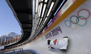 Photo - The CAN-2 sled from Canada takes a turn during a training run for the two-man bobsled at the 2014 Winter Olympics, Thursday, Feb. 6, 2014, in Krasnaya Polyana, Russia. (AP Photo/Michael Sohn)