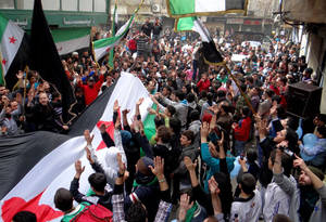 "Photo - In this citizen journalism image provided by Aleppo Media Center AMC which has been authenticated based on its contents and other AP reporting, anti-Syrian regime protesters raise up their hands as they wave  Syrian revolutionary flags during a protest to mark the second anniversary of the their uprising, in Aleppo, Syria, Friday March 15, 2013. The chief of Syria's main, western-backed rebel group marked the second anniversary of the start of the uprising against President Bashar Assad on Friday by pledging to fight until the ""criminal"" regime is gone. (AP Photo/Aleppo Media Center, AMC)"