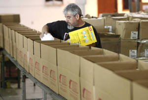 Photo - Adolfo Duran loads boxes with cleaning supplies at the Feed The Children warehouse on Nov. 1. The items were to be shipped to New Jersey after Superstorm Sandy. The Feed The Children charity has been honored with a 2012 Top-Rated Award by GreatNonprofits. Photo By David McDaniel, The Oklahoman Archives