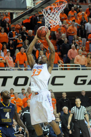 Photo - Oklahoma State guard Marcus Smart scores against West Virginia during an NCAA college basketball game in Stillwater, Okla., Saturday, Jan. 26, 2013. (AP Photo/Tulsa World, KT King)  ONLINE OUT; TV OUT; TULSA OUT