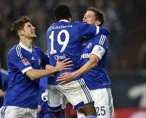 Photo - Schalke's Klaas-Jan Huntelaar of the Netherlands, right, celebrates his goal with teammate Leon Goretzka, left, and Chinedu Obasi of Nigeria during  the German Bundesliga soccer match between FC Schalke 04 and Hertha BSC Berlin in Gelsenkirchen, Germany, Friday March 28, 2014. (AP Photo/Martin Meissner)