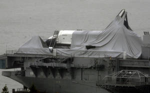 Photo -   The space shuttle Enterprise is draped with cloth that had protected it before Superstorm Sandy passed though, leaving the spacecraft shrouded on the deck of the Intrepid Sea, Air & Space Museum, at its dock on the Hudson River in New York, Tuesday, Oct, 30, 2012. Sandy, the storm which was downgraded from a hurricane just before making landfall, caused multiple fatalities, halted mass transit and cut power to more than 6 million homes and businesses. (AP Photo/Peter Morgan)