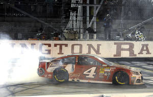 Photo - Kevin Harvick does a burnout after winning the NASCAR Sprint Cup auto race at Darlington Raceway in Darlington, S.C., Saturday, April 12, 2014. (AP Photo/Mike McCarn)