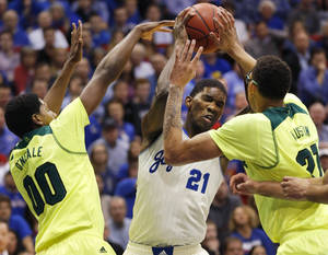 Photo - Kansas center Joel Embiid (21) looks for a shot while covered by Baylor forward Royce O'Neale (00) and center Isaiah Austin (21) during the first half of an NCAA college basketball game in Lawrence, Kan., Monday, Jan. 20, 2014. (AP Photo/Orlin Wagner)