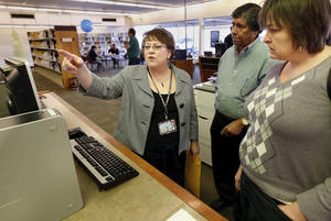 Photo - Almonte Library Manager LaVetta Dent explains operation of the computer reservation system to Jay Ramanjula and Dana Tuley-Williams during the grand reopening of the library. Photos by Steve Sisney, The Oklahoman