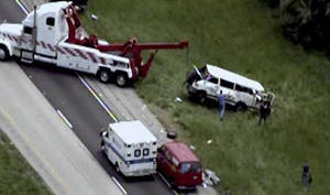 Photo - This photo from video provided by KMOV-TV in St. Louis shows emergency personnel at the scene near Vandalia, Ill., Monday, May 20, 2013, where a van veered off a southern Illinois highway and overturned several times, killing five people and sending six others to hospitals, authorities said. Details about what caused the crash or who owned the white 2002 Dodge van, which had no decals or displayed markings, were not immediately available. (AP Photo/Courtesy KMOV-TV in St. Louis)  ST LOUIS POST DISPATCH OUT. TV OUT