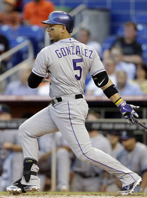 Photo - Colorado Rockies' Carlos Gonzalez follows through on an RBI-double to score Michael Cuddyer in the first inning of a baseball game against the Miami Marlins, Wednesday, April 2, 2014, in Miami. (AP Photo/Lynne Sladky)