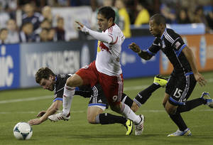 Photo - From left, San Jose Earthquakes' Mike Fucito, New York Red Bulls' Juninho (9), and Earthquakes' Justin Morrow (15) chase a loose ball during the first half of an MLS soccer game Sunday, March 10, 2013, in Santa Clara, Calif. (AP Photo/Ben Margot)