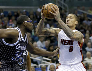 Photo - Miami Heat's Michael Beasley (8) goes up for a shot as he is defended by Orlando Magic's Jason Maxiell (54) during the first half of an NBA basketball game, Saturday, Jan. 4, 2014, in Orlando, Fla. (AP Photo/John Raoux)