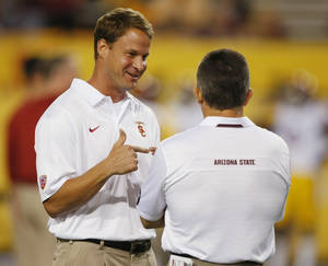 "Photo - FILE - Southern California coach Lane Kiffin talks to Arizona State coach Todd Graham before an NCAA college football game in a Saturday, Sept. 28 2013, file photo, in Tempe, Ariz. USC has fired football coach Lane Kiffin, the Trojans announced early Sunday, Sept. 29, 2013. Athletic director Pat Haden said in a short news release that he informed Kiffin of the decision ""upon the team charter's arrival back in Los Angeles early Sunday morning following USC's 62-41 loss at Arizona State.""  (AP Photo/Rick Scuteri, File)"