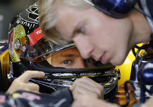 Photo -   Red Bull Formula One driver Sebastian Vettel of Germany talks to a team mechanic as he waits to start in the third practice session for the Singapore Formula One Grand Prix on the Marina Bay City Circuit in Singapore, Saturday, Sept. 22, 2012. (AP Photo/Mark Baker)