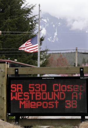 Photo - A road sign advising the closure of Highway 530 stands in view of a flag still at half-staff Tuesday, April 15, 2014, in Darrington, Wash. One more victim has been recovered from the mudslide that hit the nearby town of Oso, Wash., March 22, raising the death toll to 37, the Snohomish County medical examiner's office said Tuesday. Seven people remain on the missing list, the sheriff's office said. (AP Photo/Elaine Thompson)
