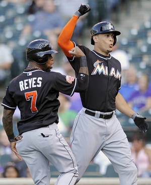 Photo -   Miami Marlins Jose Reyes, left, celebrates with teammate Giancarlo Stanton, right, after Stanton hit a three-run home run in the first inning of a baseball game against the Colorado Rockies in Denver on Saturday, Aug. 18, 2012. (AP Photo/Chris Schneider)