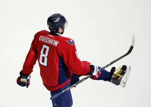 Photo - Washington Capitals right wing Alex Ovechkin (8), from Russia, celebrates his game-winning goal in the overtime period of an NHL hockey game against the Detroit Red Wings, Sunday, Feb. 2, 2014, in Washington. The Capitals won 6-5. (AP Photo/Alex Brandon)
