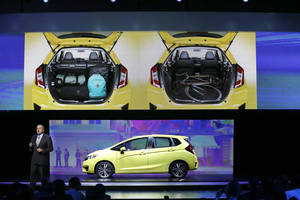 Photo - American Honda Motor Co., Executive Vice President John Mendel unveils the 2015 Honda Fit at the North American International Auto Show in Detroit, Monday, Jan. 13, 2014. (AP Photo/Carlos Osorio)