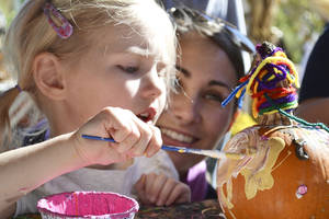 photo - Left: Kaitlyn Zabrocki, 4, of Edmond, plasters her pumpkin with white and yellow paint while her mom, Amanda, looks on Saturday at the Myriad Botanical Gardens. Photos by Zeke Campfield, The Oklahoman