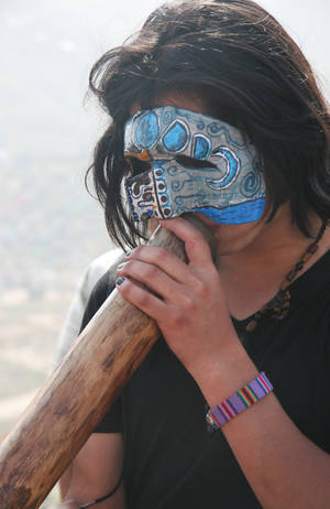 Photo - In this Nov. 1, 2012 photo, Semilla Solar Amarillo, an interior designer, plays the didgeridoo during the procession of Santa Muerte during the Day of the Dead festival at the Cemetery of Nueva Esperanza in Villa Maria del Triunfo in Lima, Peru. (AP Photo/Jody Kurash)