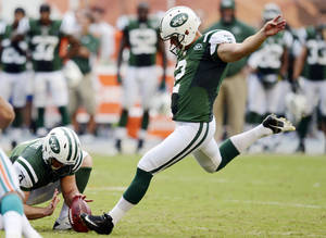 Photo -   New York Jets kicker Nick Folk (2) makes the game-winning field goal in overtime of an NFL football game against the Miami Dolphins, Sunday, Sept. 23, 2012, in Miami. Holding is punter Robert Malone (3). The Jets won 23-20. (AP Photo/Rhona Wise)