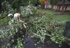 photo - Glenn Hoffman tries to clear Symmes  Street of trees that fell across the road as a result of a severe storm on Tuesday, June 14, 2011, in Norman, Okla.  Photo by Steve Sisney, The Oklahoman ORG XMIT: KOD