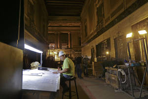 Photo - Robert Junker, a construction superintendent, looks over plans as workers perform renovation work at the Saenger Theater in Downtown New Orleans on Wednesday, May 22, 2013. (AP Photo/Gerald Herbert)