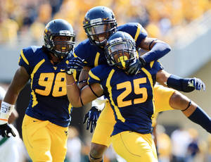 Photo - West Virginia's Pat Miller (6) celebrates Darwin Cook's (25) interception as Will Clarke (98) watches during their NCAA college football game against Baylor in Morgantown, W.Va., Saturday, Sept. 29, 2012. (AP Photo/Christopher Jackson)   ORG XMIT: WVCJ107
