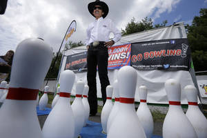 """Photo - Former NASCAR great known as """"The King,"""" Richard Petty stands near bowling pins at an outdoor lane set up at Pocono Raceway, Saturday, Aug. 2, 2014, Long Pond, Pa. (AP Photo/Mel Evans)"""