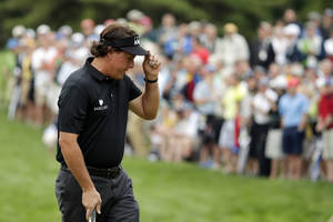 Photo - Phil Mickelson tips his hat on the 12th green during the first round of the U.S. Open golf tournament at Merion Golf Club, Thursday, June 13, 2013, in Ardmore, Pa. (AP Photo/Charlie Riedel)