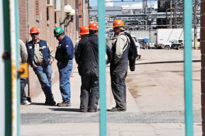 Photo -   In this photo taken May 8, 2012, workers stand outside the Sinclair Oil Refinery in Sinclair, Wyo., a day after a flash fire at the facility. Three workers were injured and remained hospitalized at North Colorado Medical Center's Western States Burn Center in Greeley, Colo. Their condition improved to fair on Friday, May 11, 2012. A fourth worker was treated and released from Memorial Hospital of Carbon County in Rawlins on Tuesday. (AP Photo/The Rawlins Daily Times, Zachary Laux)