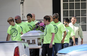 Photo - FILE - In this Monday, Sept. 16, 2013 file photo, pallbearers wearing anti-bullying T-shirts carry the casket of Rebecca Sedwick,12, to a waiting hearse as they exit the Whidden-McLean Funeral Home in Bartow, Fla. One of two teenage girls charged with stalking Rebecca Sedwick, a Florida classmate who complained of being bullied before her suicide no longer faces any criminal counts, her attorney said Wednesday, Nov. 20, 2013. (AP Photo/Brian Blanco, File)