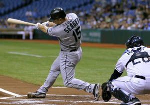 Photo -   Seattle Mariners' Kyle Seager follows through on his first-inning, three-run home run off Tampa Bay Rays starting pitcher James Shields during a baseball game, Wednesday, May 2, 2012, in St. Petersburg, Fla. Mariners' Ichiro Suzuki and Jesus Montero also scored on the hit. Catching for Tampa Bay is Jose Molina. (AP Photo/Chris O'Meara)